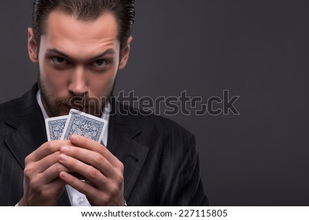 Handsome  confident man   holding cards  looking at  camera  with copy place