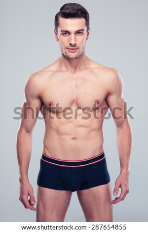 Handsome confident man with muscular body standing over gray background and lookign at camera - stock photo