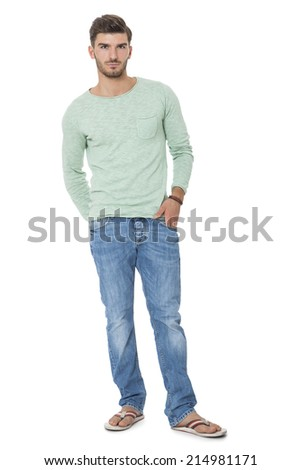 Handsome confident relaxed handsome young man with a beard posing with his hands in his pockets in jeans and slip slops, isolated on white - stock photo