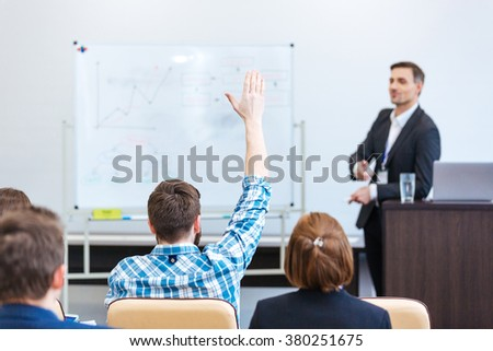 Handsome confident teacher lecturing and tallking to students in univercity - stock photo