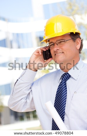 Handsome Contractor in Hardhat and Necktie Smiles as He Talks on His Cell Phone. - stock photo