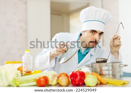 handsome cook tasting soup with ladle from pan in kitchen - stock photo