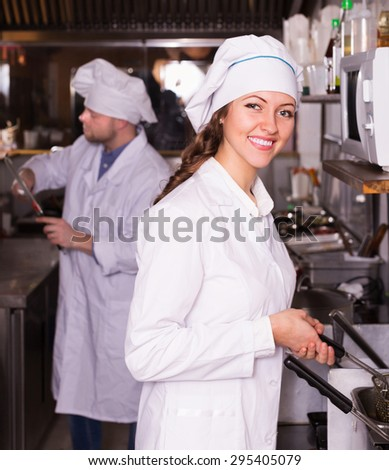 Handsome cooks greeting customers at bistro kitchen and smiling - stock photo