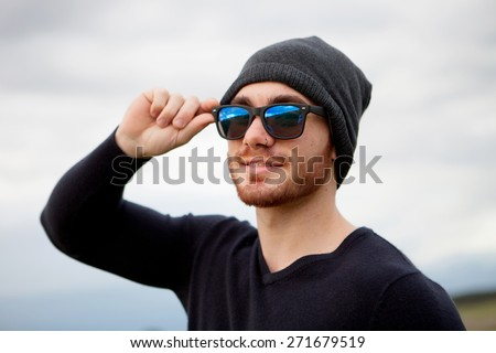 Handsome cool young man with sunglasses and cap wool - stock photo