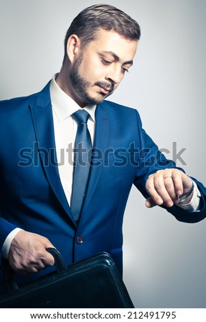 Handsome corporate businessman checking the time on his watch