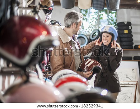 handsome couple choosing a trendy motorcycle's helmet in a specialized shop - stock photo