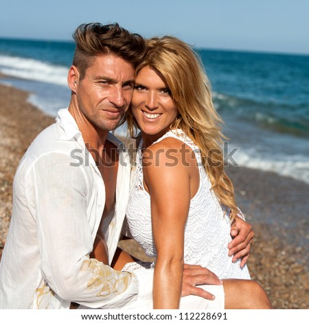 Handsome couple enjoying afternoon sun on beach. - stock photo