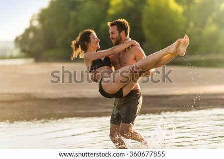 Handsome couple having fun in the water at the beach during the holidays. The man is shirtless and the woman has a black bikini. He is carrying her in his arms above the water.Backlit shot - stock photo