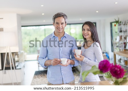 handsome couple is drinking tea and coffee at home - stock photo
