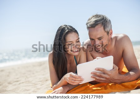 handsome couple on the seaside lying on a beach towel to use a digital tablet - stock photo
