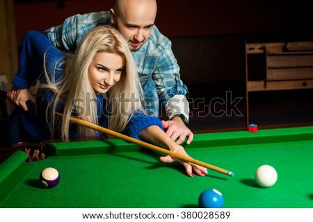 Handsome couple plays billiard on the pool table. American pool billiard. Billiard sport concept. Pool billiard game. - stock photo