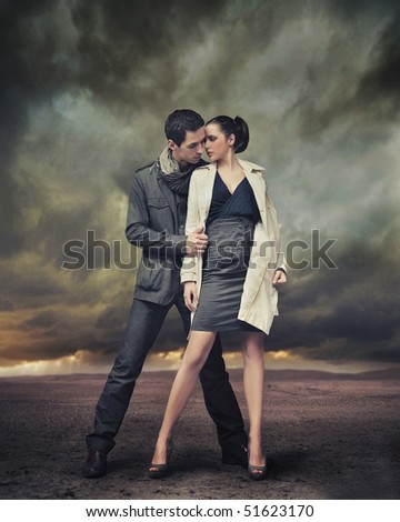 Handsome couple posing over stormy background - stock photo
