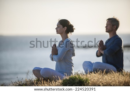 handsome couple practicing meditation exercises on the beach at sunset - stock photo