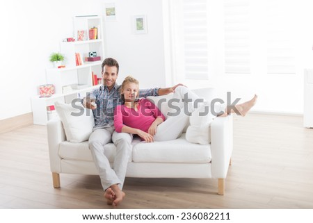 Handsome couple relaxing barefoot on a white sofa and using remote control for a tv - stock photo