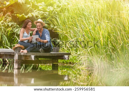 handsome couple sitting on a wooden pontoon on a river in summertime, they are using a digital tablet - stock photo