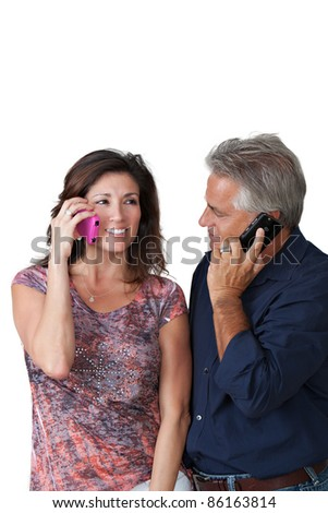 Handsome couple talking on cell phone - stock photo