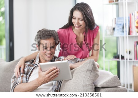 handsome couple using digital tablet on a couch - stock photo