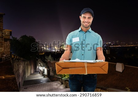 Handsome courier man with parcel against cityscape by night - stock photo