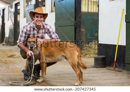handsome cowboy and his dog inside stables  - stock photo