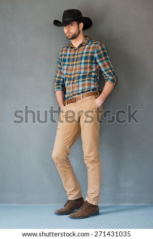 Handsome cowboy. Full length of handsome young man wearing cowboy hat and holding hands in pockets while leaning grey background  - stock photo
