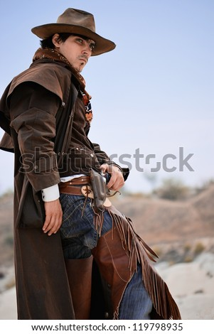 handsome cowboy in specific clothing with weapon. outdoor shot - stock photo
