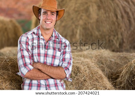 handsome cowboy standing against hay bales - stock photo