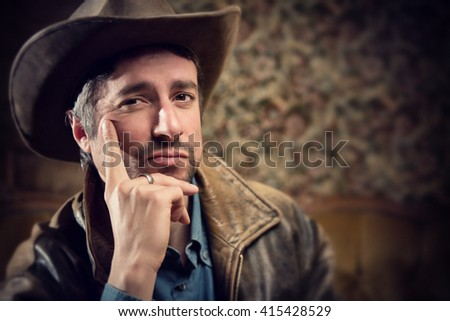 handsome cowboy with sensual gaze and hat in a old house