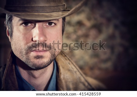 handsome cowboy with sensual gaze and hat in a old house - stock photo