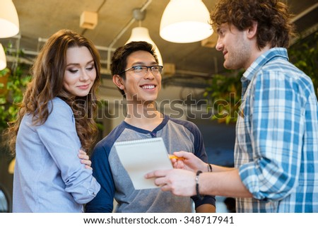 Handsome curly excited young man showing his notes in notepad to his young colleagues in the office - stock photo