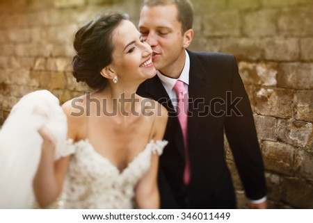 Handsome cute groom kissing smiling  beautiful brunette bride cl - stock photo