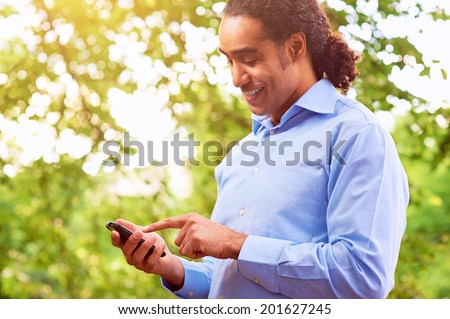 Handsome dark skin man dialing a number on the smartphone. - stock photo