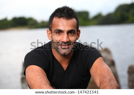 Handsome dark-skinned man with a beard smiles while sitting near a reservoir
