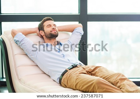 Handsome day dreamer. Handsome young man holding hands behind head while sleeping on the couch  - stock photo