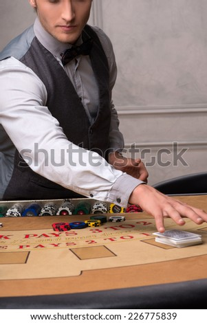 Handsome  dealer  laying cards and   chips on  table with  red blue and white chips in piles in casino