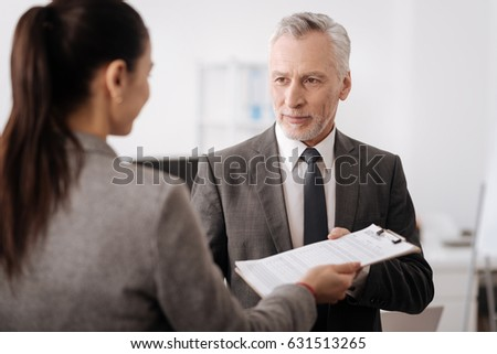 Handsome delighted male person taking documents