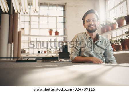 Handsome designer entrepreneur smiling at the camera while relaxing in his studio with gentle sun flare coming in through the window - stock photo