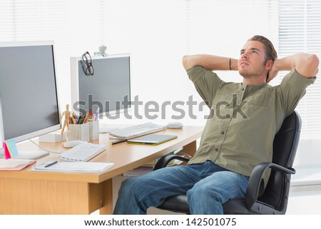 Handsome designer leaning back at his desk in a modern office - stock photo