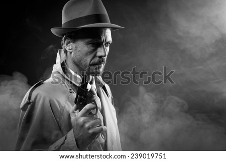 Handsome detective in trench coat holding a gun in the dark, film noir - stock photo