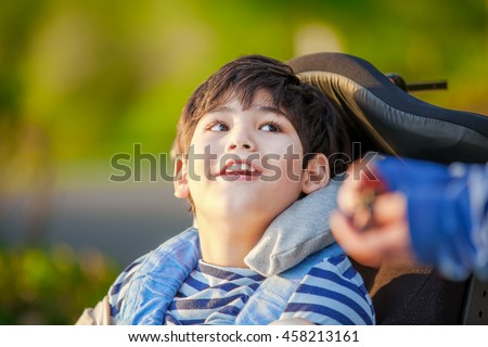 Handsome disabled nine year old boy sitting in wheelchair outdoors looking up into sky  - stock photo