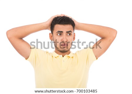 Handsome disappointed young man putting his hands on his head, guy wearing yellow t-shirt and jeans, isolated on white background