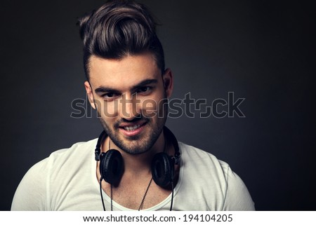 Handsome DJ posing in studio on dark background with headphones around neck - stock photo