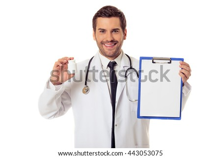 Handsome doctor in white coat is holding a folder and a bottle of medicine, looking at camera and smiling, isolated on white background