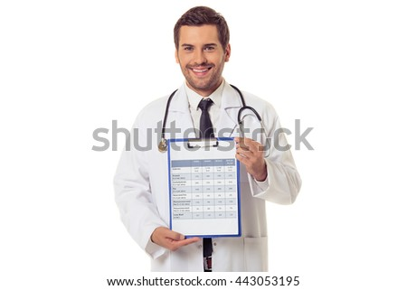 Handsome doctor in white coat is holding a folder with data, looking at camera and smiling, isolated on white background