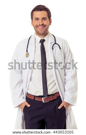 Handsome doctor in white coat is looking at camera and smiling while standing with hands in pockets, isolated on white background