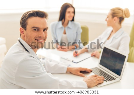Handsome doctor is using a laptop, looking at camera and smiling. In the background female doctor is giving a consultation to woman