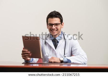 Handsome Doctor Looking At His Computer Monitor In His Office - stock photo