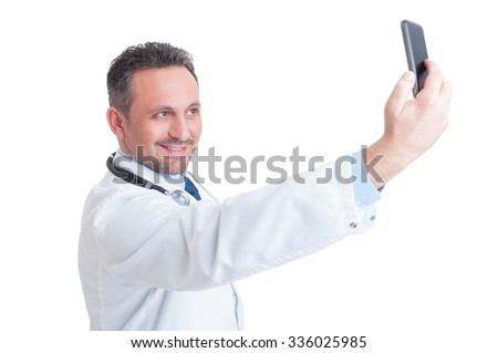Handsome doctor or medic taking a selfie with front camera smiling isolated on white background