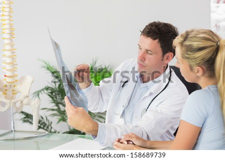 Handsome doctor showing a patient something on x-ray in bright office - stock photo