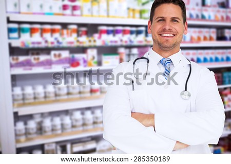 Handsome doctor with arms crossed against close up of shelves of drugs - stock photo