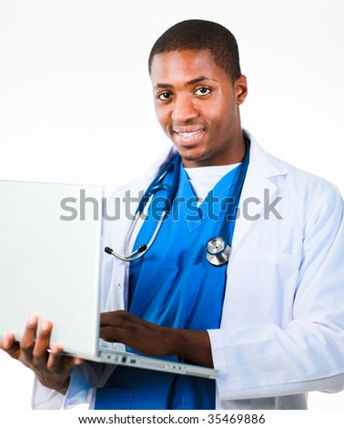 Handsome doctor working on a laptop and smiling at the camera - stock photo